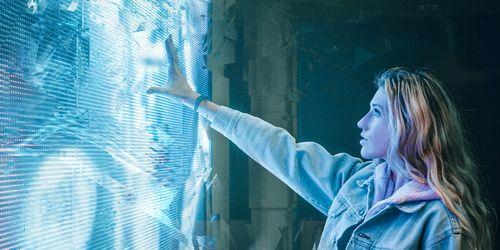 Woman touching futuristic wall